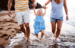 A midsection of parents with toddler daughter walking on beach on summer holiday. A midsection of parents with toddler daughter walking on beach on summer stock image