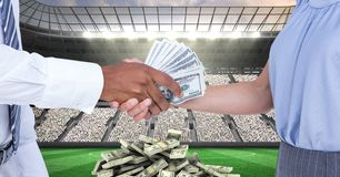 Midsection of people exchanging money at football stadium representing corruption stock photography