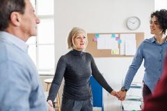 Midsection of people standing in a circle and holding hands during group therapy. royalty free stock photo
