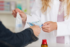 Midsection Of Pharmacist Receiving Money From Customer For Medic. Midsection of female pharmacist receiving money from customer for medicines at pharmacy Royalty Free Stock Image