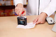 Midsection Of Pharmacist Stamping Bill At Desk Stock Photos