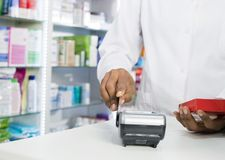 Midsection Of Pharmacist Swiping Credit Card While Holding Produ. Midsection of female pharmacist swiping credit card on reader while holding product in pharmacy Stock Images