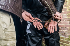 Midsection of policeman putting handcuffs on criminal`s hands at Stock Photos