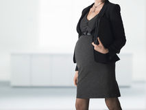 Midsection Of Pregnant Businesswoman With Folder Royalty Free Stock Images