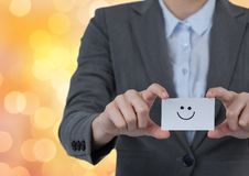 Midsection of professional holding business card with smiley face over bokeh stock photo