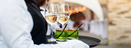Midsection of professional waiter in uniform serving wine during buffet catering party, festive event or wedding. Full. Glasses of champagne on tray stock image
