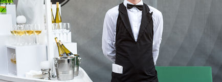 Midsection of professional waiter in uniform serving wine during buffet catering party, festive event or wedding. Full Royalty Free Stock Photo