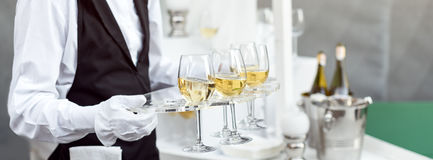 Midsection of professional waiter in uniform serving wine during buffet catering party, festive event or wedding. Full Royalty Free Stock Images