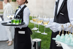 Midsection of professional waiters in uniform serving wine and snacks during buffet catering party, festive event or Stock Image