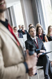 Midsection of public speaker with business people in seminar hall royalty free stock image
