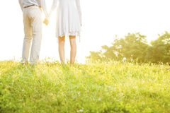 Midsection rear view of couple holding hands while standing on grass against sky Royalty Free Stock Photo