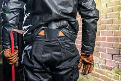 Midsection rear view of gangster with crowbar and gun standing b Royalty Free Stock Image