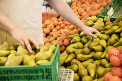 Midsection Of Salesman Arranging Fresh Pears Stock Photography