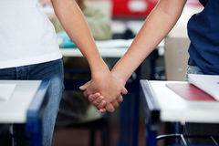 Midsection Of Schoolboy And Girl Holding Hands At Royalty Free Stock Images