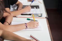 Midsection Of Schoolchildren Writing At Desk Stock Images