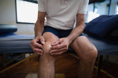 Midsection of senior male patient holding knee in pain. At hospital ward Stock Images