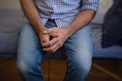Midsection of senior male patient sitting with hands clasped on bed Stock Photography