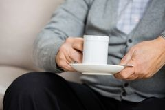 Midsection Of Senior Man Holding Coffee Cup On Royalty Free Stock Images