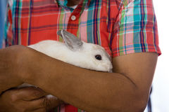 Midsection of senior man holding rabbit. At retirement home Stock Photo