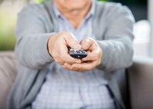 Midsection Of Senior Man Holding TV Remote Control. Midsection of senior man using TV remote control while sitting on couch in nursing home royalty free stock photo
