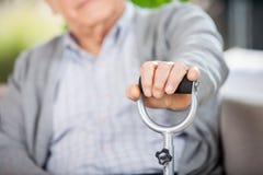 Midsection Of Senior Man Holding Walking Stick. At nursing home royalty free stock images