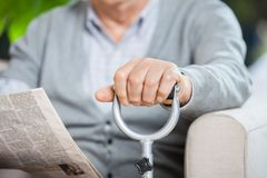 Midsection Of Senior Man With Newspaper And Cane. Midsection of senior man with newspaper and metal cane sitting on couch at nursing home porch royalty free stock images