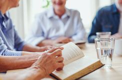 Midsection of senior people in bible reading group in community center club. royalty free stock photo