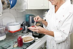 Midsection of senior woman applying jam on toast in kitchen Stock Images