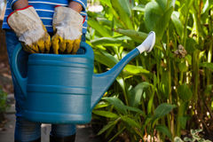 Midsection of senior woman standing with watering can against plants Royalty Free Stock Images