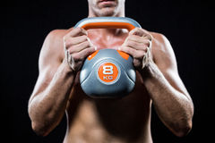 Midsection of shirtless athlete holding kettlebell Royalty Free Stock Image