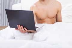 Midsection of shirtless man holding laptop in bed Stock Image