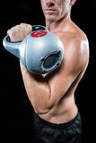 Midsection of shirtless sportsman working out with kettlebell Stock Photo