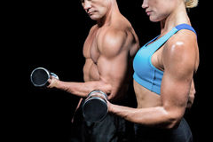 Midsection side view of man and woman lifting dumbbells Stock Photo