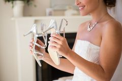 Midsection of smiling bride holding sandals in fitting room. Midsection of smiling bride holding sandals while sitting in fitting room Stock Photography