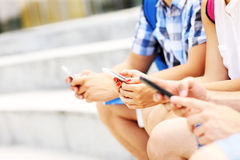 Midsection of students and their smartphones Royalty Free Stock Photos