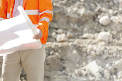 Midsection of supervisor holding blueprint at construction site Royalty Free Stock Photo