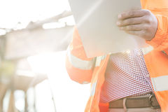 Midsection supervisor holding clipboard at construction site on sunny day Royalty Free Stock Photography