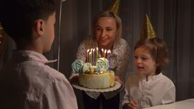 Midsection of sweet cheerful toddler boy, blowing candles on cake and clapping hands during his birthday party at home. Midsection of sweet cheerful toddler boy stock video