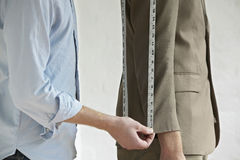 Midsection Of Tailor Measuring Customer's Suit. Midsection of young male tailor measuring customer's suit in fashion studio stock images