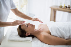 Midsection of therapist performing reiki on woman. Midsection of therapist performing reiki on young woman at spa Stock Photo