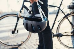 Midsection of commuter with electric bicycle and helmet traveling in city. Midsection of unrecognizable commuter with electric bicycle and helmet traveling in stock photography