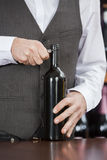 Midsection van Barman Opening Wine Bottle royalty-vrije stock afbeeldingen