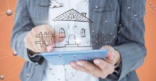 Midsection van bedrijfspersoon met huis over tabletpc Stock Afbeeldingen