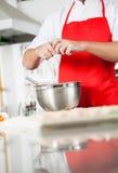 Midsection van Chef-kok Breaking Egg In die Kom mengen bij Royalty-vrije Stock Afbeelding