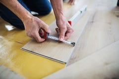 Midsection van de hogere mens die vinylbevloering, een nieuw huisconcept leggen stock fotografie