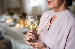 Midsection van een hogere vrouw die zich binnen die in een ruimte bevinden voor een partij wordt geplaatst, die wijn houden royalty-vrije stock foto's