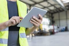 Midsection van handarbeider die digitale tablet in de metaalindustrie gebruiken royalty-vrije stock afbeelding