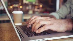 Midsection van handen die laptop in cafetaria met behulp van stock footage