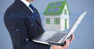 Midsection van laptop van de zakenmanholding tegen 3d huis Stock Afbeelding