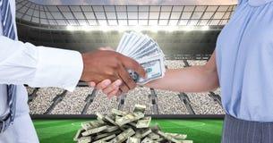 Midsection van mensen die geld ruilen bij voetbalstadion die corruptie vertegenwoordigen stock fotografie